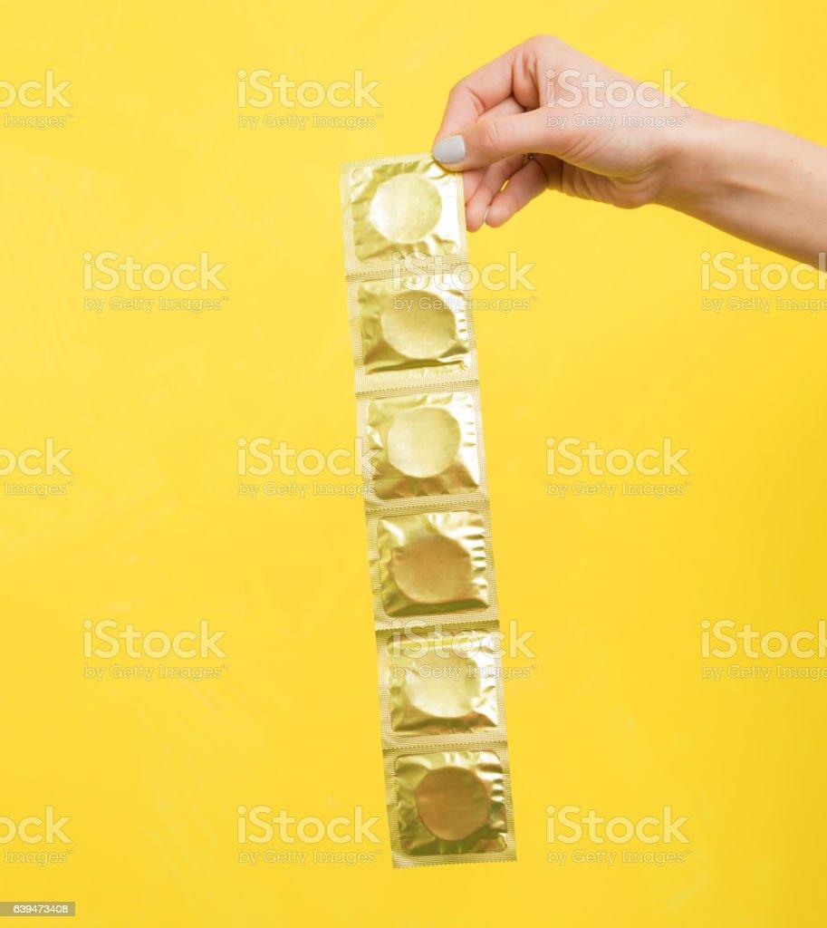 Woman holding condoms stock photo