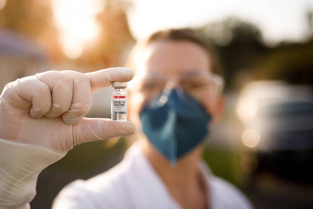 Woman holding covid-19 vaccine vial stock photo
