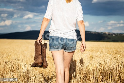 Cowgirl walking in countryside. Worn leather riding boot