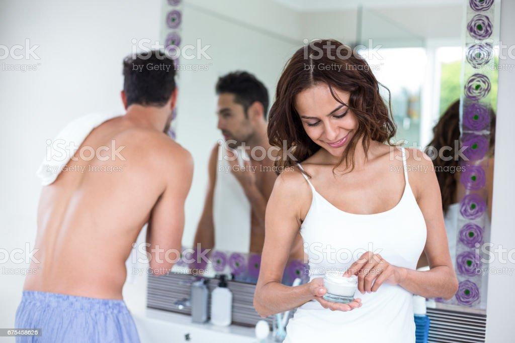 Femme tenant crème tandis que mari en arrière-plan photo libre de droits