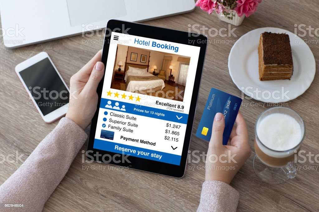 woman holding credit card and computer tablet app hotel booking stock photo