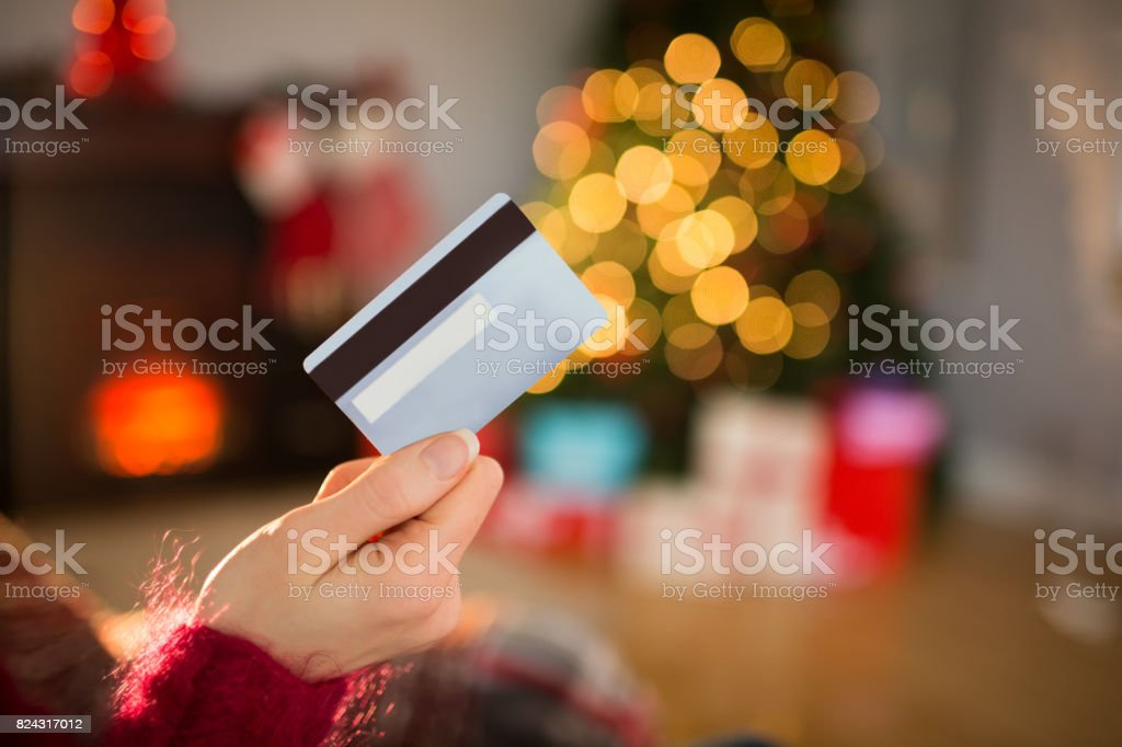 Woman holding credit card at christmas stock photo