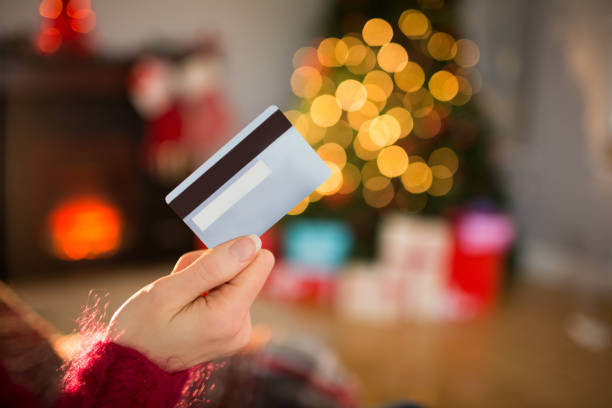 woman holding credit card at christmas - spending money stock photos and pictures