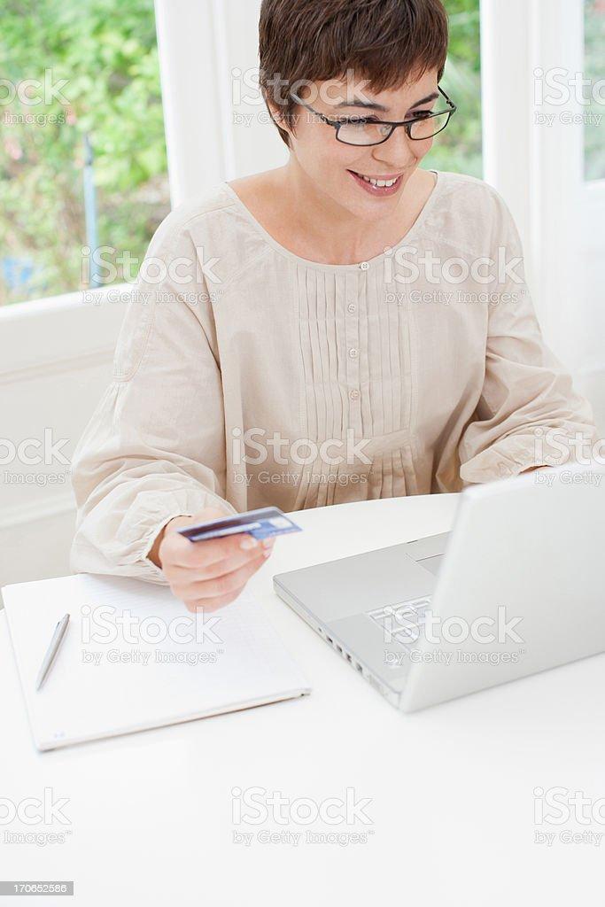 Woman holding credit card near laptop stock photo