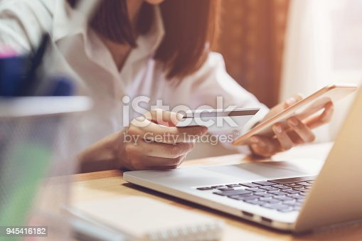 861940002 istock photo Woman holding credit card pay online and using smartphone for shop through the website. Concepts online shopping for convenience. 945416182