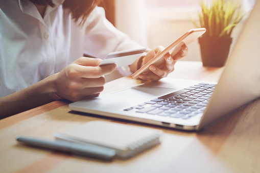 istock Woman holding credit card pay online and using smartphone for shop through the website. Concepts online shopping for convenience. 968631180