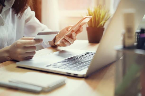 woman holding credit card pay online and using smartphone for shop through the website. concepts online shopping for convenience. - online shopping imagens e fotografias de stock