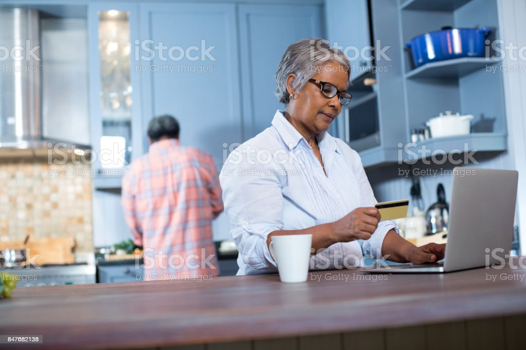 Woman holding credit card while using laptop stock photo