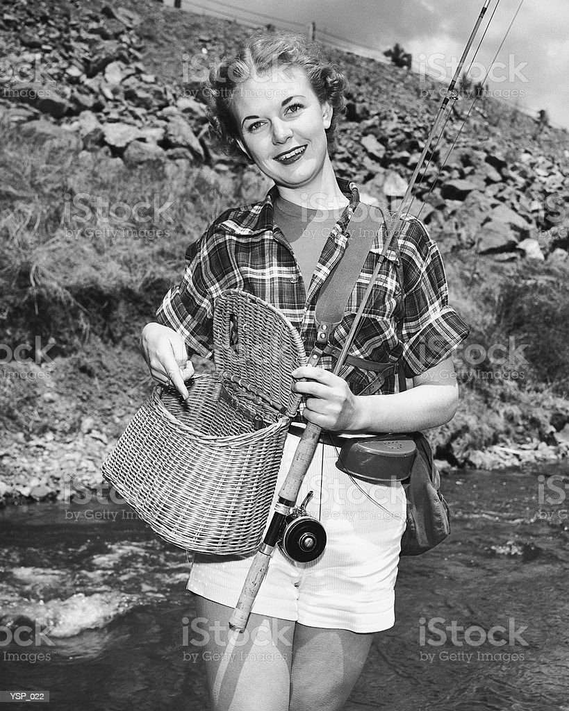 Woman holding creel and fishing rod royalty-free stock photo