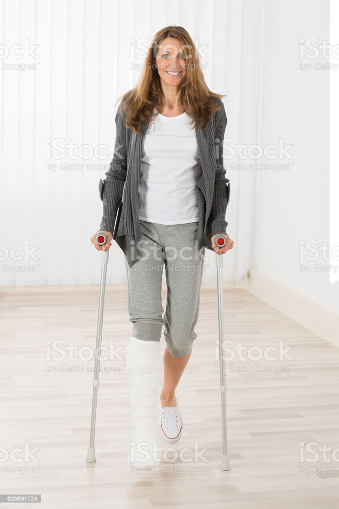 Woman Holding Crutches While Walking stock photo