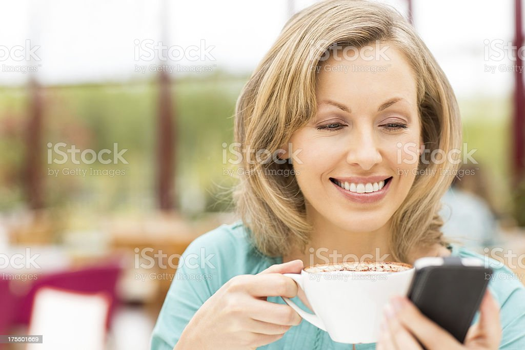 Woman Holding Cup Of Coffee And Cell Phone royalty-free stock photo