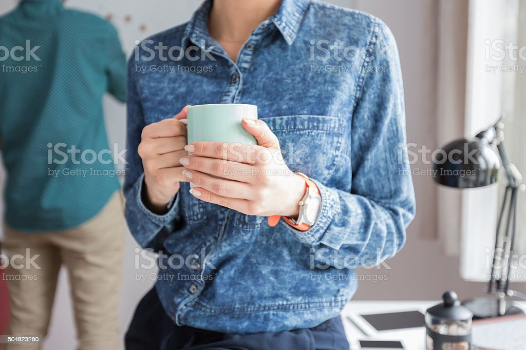Woman holding cup of coffee, close up of hands Woman wearing jeans shirt holding a cup of coffee in an office, close up of hands, unrecognizable person. Defocused man in the background. Adult Stock Photo