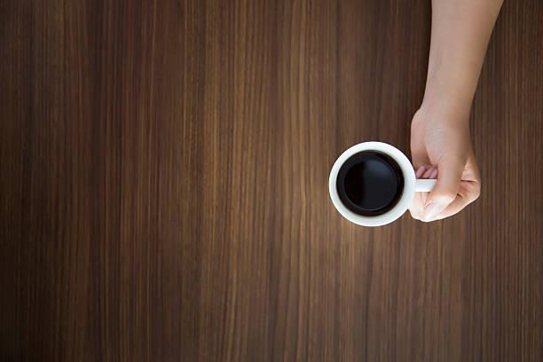 Frau hält eine Tasse Kaffee latte auf einem Holztisch – Foto