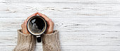 istock Woman holding cup of hot coffee on rustic wooden table, closeup photo of hands in warm sweater with mug, winter morning concept, top view. Banner 1024167012