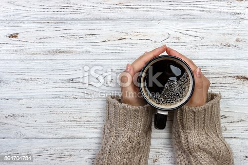 istock Woman holding cup of hot coffee on rustic wooden table, closeup photo of hands in warm sweater with mug, winter morning concept, top view 864704784