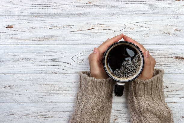 woman holding cup of hot coffee on rustic wooden table, closeup photo of hands in warm sweater with mug, winter morning concept, top view - coffee stock pictures, royalty-free photos & images