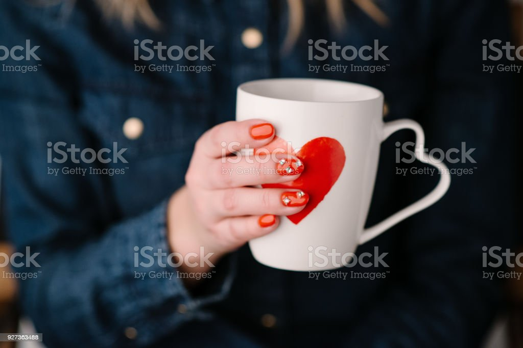 Woman holding  cup  with heart shape. Close up - Royalty-free Adult Stock Photo