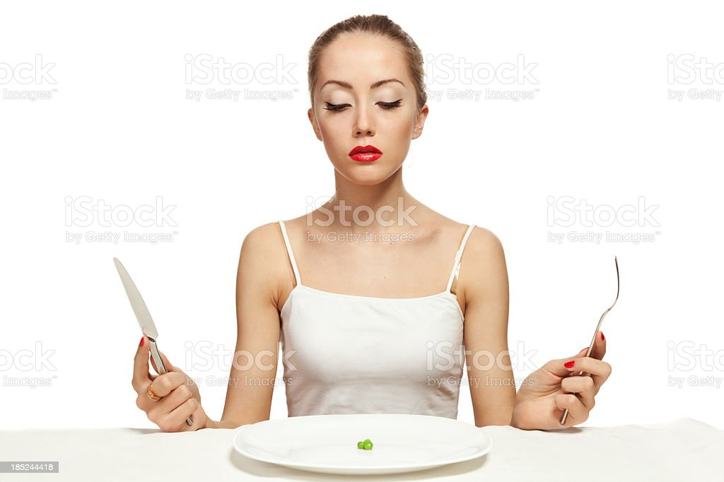 Woman holding cutlery and a white plate with a single pea royalty-free stock photo