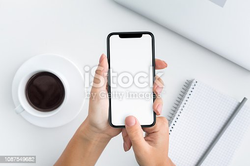 istock Woman holding device and touching blank screen 1087549682