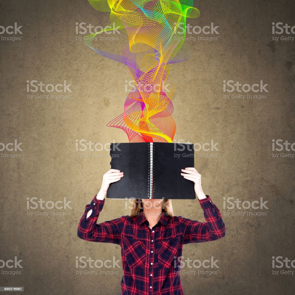 Woman holding diary in front of her face stock photo