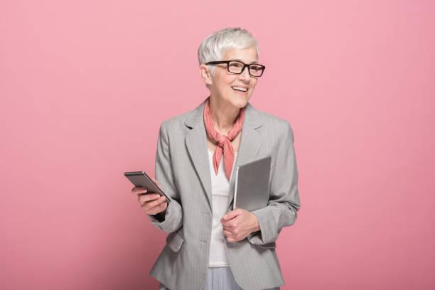 woman holding digital tablet and mobile phone - senior business woman tablet imagens e fotografias de stock