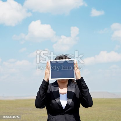 Woman holding digital tablet outdoors