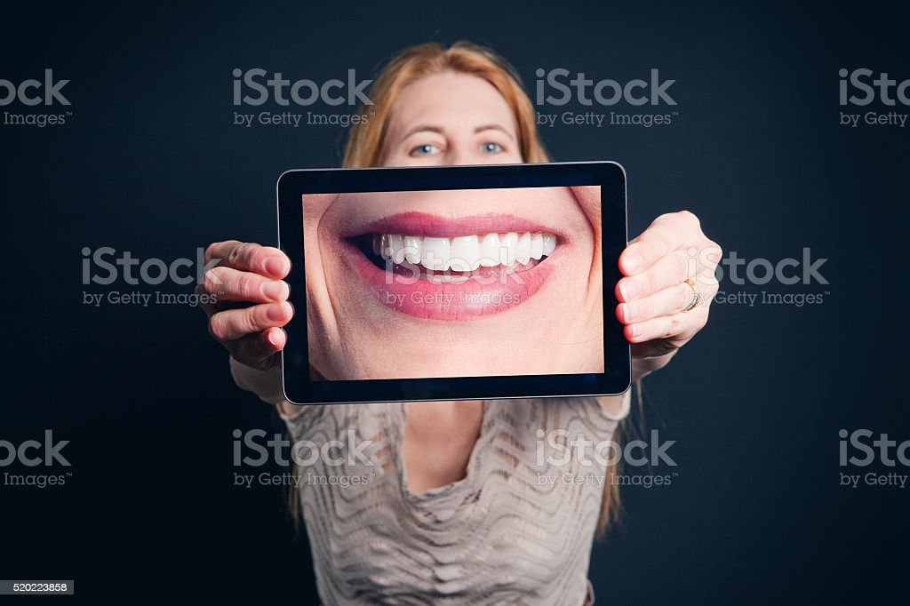 Woman Holding Digital Tablet With Teeth Picture stock photo