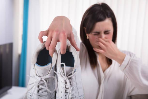 Woman Holding Dirty Smelling Shoes stock photo