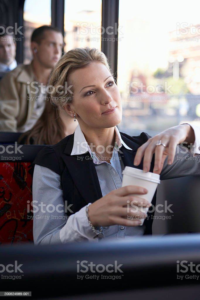 Woman holding disposable cup on bus stock photo