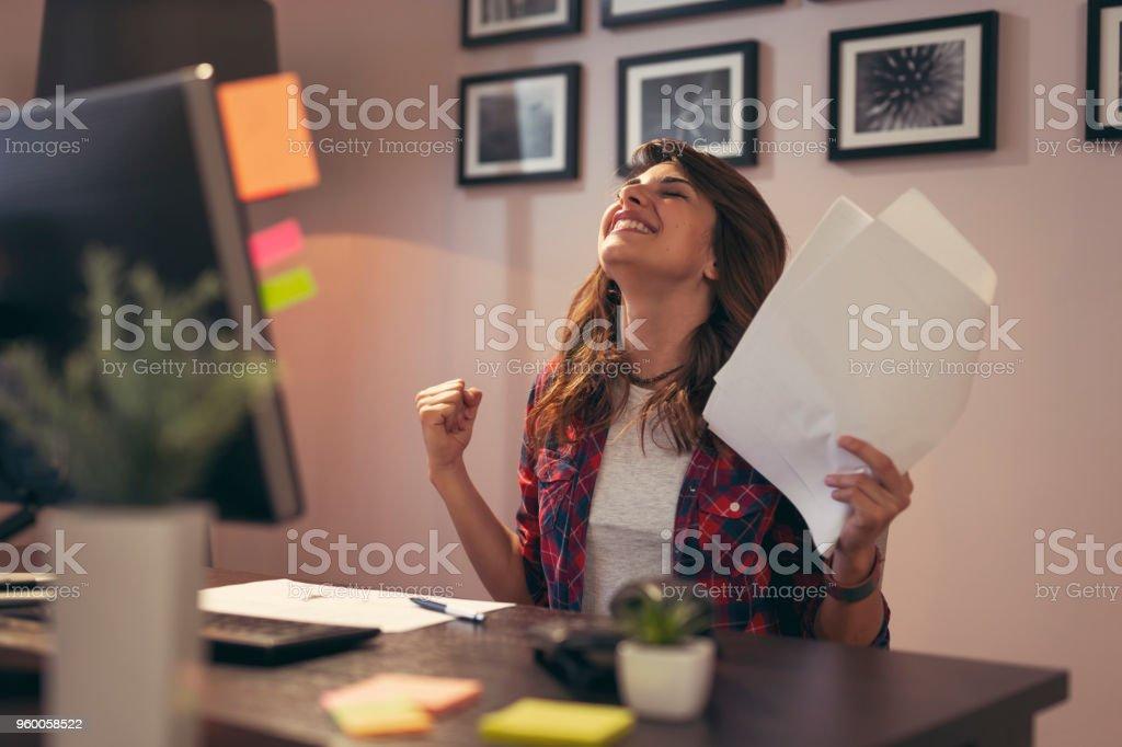 Woman holding documents joyful after a business success stock photo