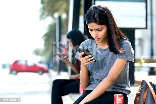 Beautiful woman holding drink can and text messaging on mobile phone