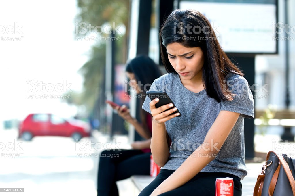 Woman holding drink can and texting on mobile phone stock photo