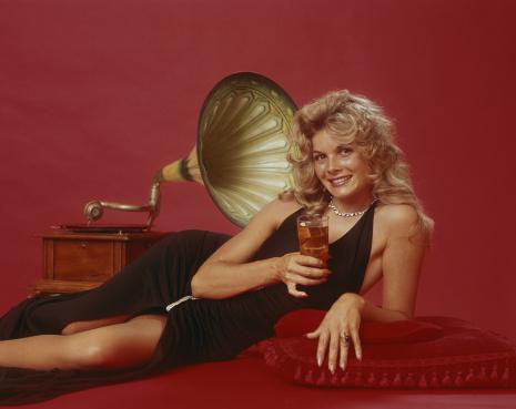 Woman holding drink leaning beside gramophone, portrait