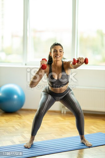 1035512048istockphoto Woman holding dumbbells and smiling 1195777018