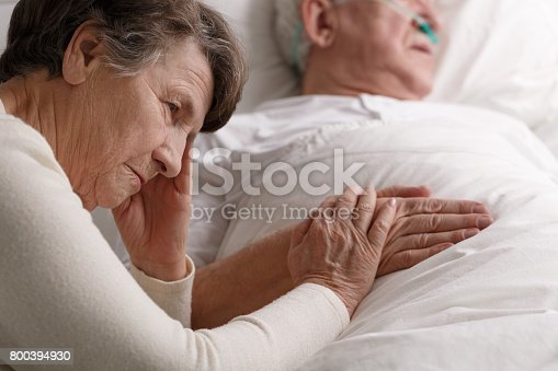 909569706istockphoto Woman holding dying husband's hand 800394930