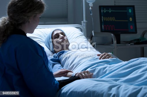 910488902istockphoto Woman holding dying mother's hand 948333920