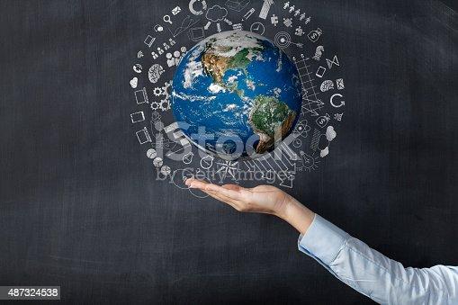 638813890istockphoto Woman holding earth front of blackboard 487324538