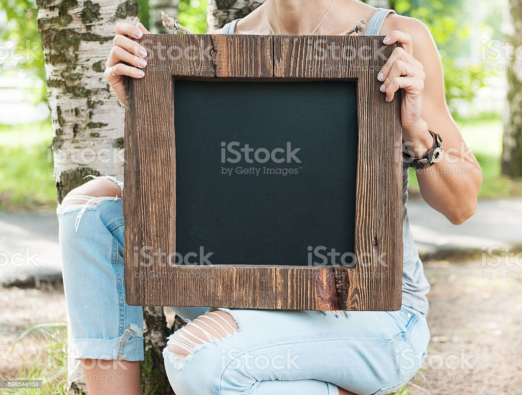 Woman holding empty blackboard with wooden frame. Template Mock photo libre de droits
