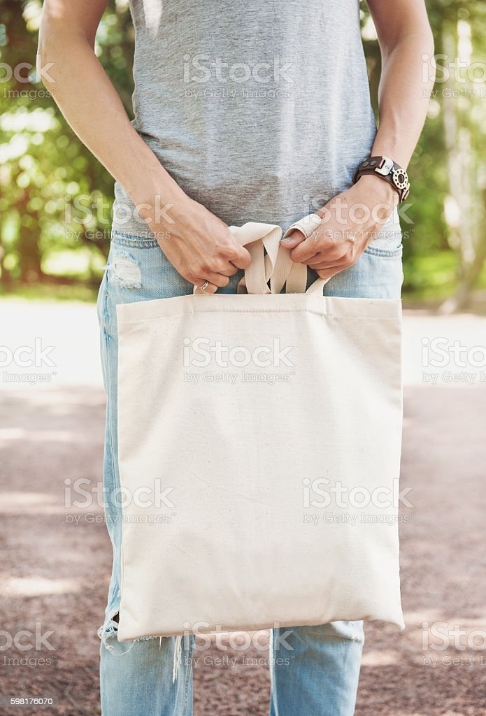 Woman holding empty canvas bag. Template mock up stock photo