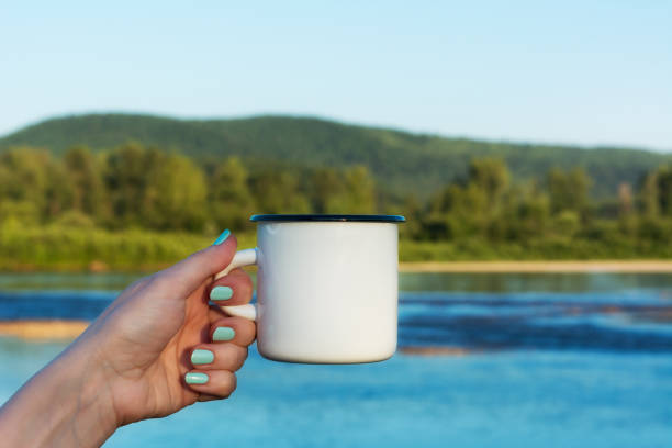 Woman holding enamel mug with river view stock photo