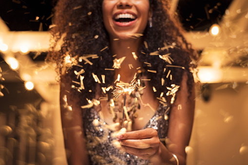 Cheerful young woman holding single sparkler in hand outdoor. Detail of african girl celebrating new year\