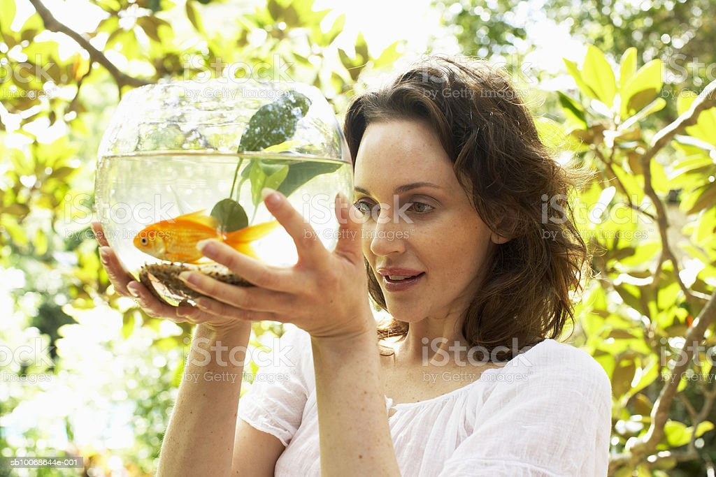 Woman holding fish bowl, smiling 免版稅 stock photo