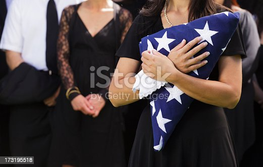 A woman holding a folded American flag at a funeral.