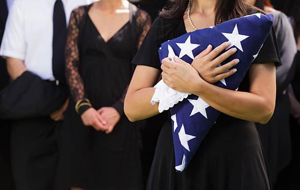 femme tenant un drapeau à des funérailles - veuve photos et images de collection