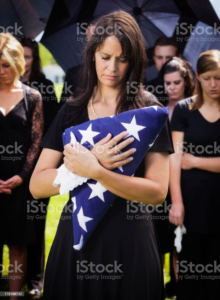Woman Holding Flag at a Funeral royalty-free stock photo