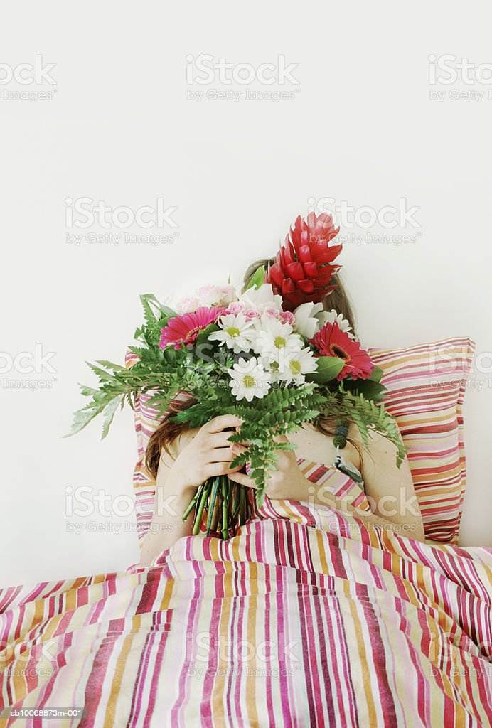 Woman holding flowers on bed photo libre de droits