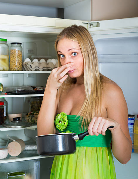 Woman holding foul food near fridge Blonde young woman holding her nose because of bad smell near fridge at home addle stock pictures, royalty-free photos & images