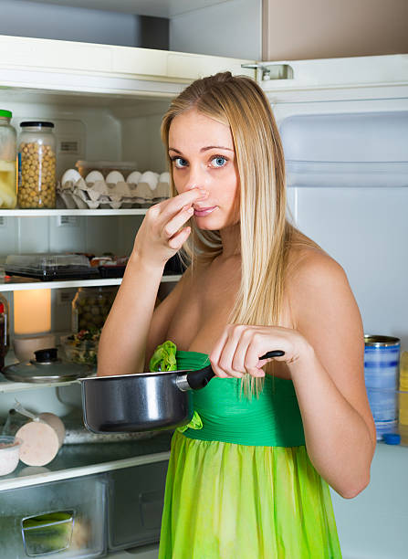 Woman holding foul food near fridge Girl holding her nose because of bad smell from food near refrigerator at home addle stock pictures, royalty-free photos & images