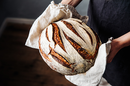 Close-up of fresh baked sourdough bread. Woman is holding wheat and rye beard. She is in kitchen.