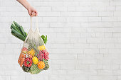 istock Woman holding fresh vegetables over white bricks wall in eco shopping bag 1186260961